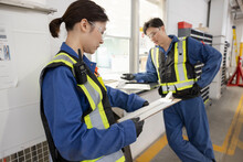 Workers With Clipboards In Maintenance Facility