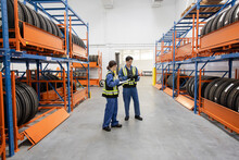 Workers Looking At Tires In Maintenance Facility Warehouse