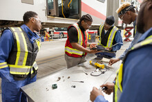 Engineers And Mechanics Fixing Bus In Maintenance Facility