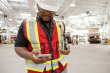 Male Supervisor With Smart Phone In Bus Transit Garage