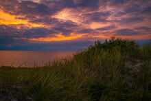 Blazing Sunset With Dramatic Cloudscape Over The Grassy Sand Dunes In The Shore On Cape Cod
