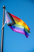Close Up Of Rainbow LGBT Flag Fluttering On Blue Sky Background