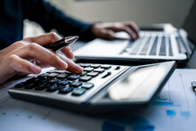 Close Up Of Businesswomen Or Accountant Using A Calculator Calculates And Laptop Computer While Working Analytic Business Report On The Workplace, Planning Financial And Accounting Concept.