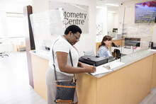 Female Patient Filling Out Paperwork At Optometry Center Front Desk