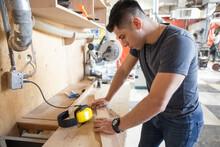 Male Woodworker With Wood Board In Workshop