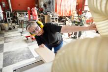 Senior Female Woodworker In Ear Protectors In Wood Shop