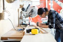 Female Woodworker Measuring Wood Plank In Wood Shop