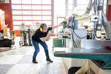 Female Woodworker Putting Wood Into Planer Machine In Wood Shop