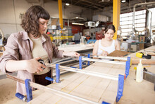 Female Woodworkers Using Bar Clamps On Wood In Workshop