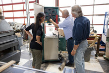 Woodworkers Inspecting Bandsaw Equipment In Workshop