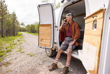 Man Talking On Phone In Campervan In Forest