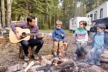 Man Playing Guitar And Singing With Children Next To Campfire
