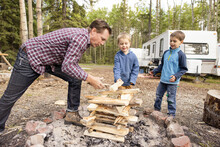Father Building Fire In Forest With Children