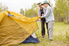 Sisters Setting Up Tent In Forest