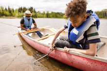 Father And Son Fishing In Canoe On River