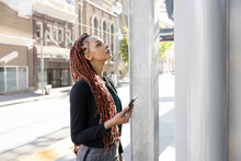Young Woman With Smart Phone Looking Up At Bus Stop In City