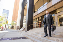 Businessman With Briefcase Descending Steps In City