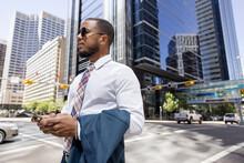 Stylish Businessman With Smart Phone On City Street Corner