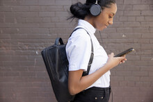 Young Woman With Backpack And Headphones Using Smart Phone