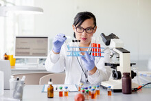 Female Scientist With Test Tube Rack In Laboratory