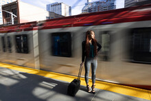 Young Businesswoman With Suitcase At Moving Train In City
