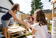 Mother Giving Daughter Glass Of Water On Sunny Summer Patio