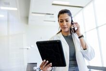 Female Scientist In Lab Coat With Digital Tablet Talking On Phone