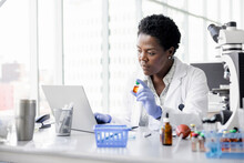 Female Scientist With Vial Working At Laptop In Laboratory