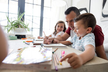 Father And Children Coloring At Living Room Coffee Table
