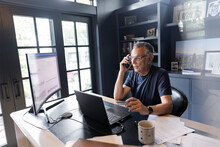 Senior Man Talking On Smart Phone At Laptop In Home Office
