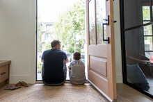 Father And Son Sitting In Open Front Door