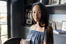 Portrait Smiling Woman Drinking Coffee In Home Office