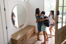 Mother Hugging Daughters With Backpacks At Front Door