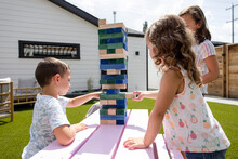 Brother And Sisters Playing Block Removal Game At Sunny Patio Table