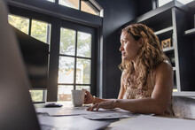 Woman With Coffee Working At Computer In Home Office