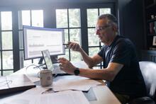 Senior Man Talking On Speaker Phone At Desk In Home Office