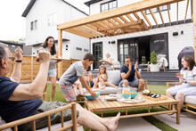 Multigenerational Family Cheering In Backyard