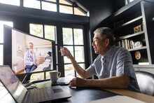 Senior Man With Prescription Video Chatting With Doctor On Computer