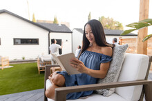 Woman Reading Book In Armchair On Patio
