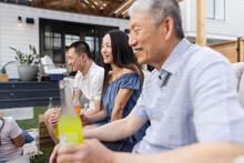 Multigenerational Family Drinking Soda On Patio