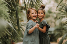 Two Cute Smiling Little Girls Belonging To Different Races, In Linen Clothes, Holding Hands And Walking In The Botanical Garden. Children Explore Tropical Plants And Flowers In The Greenhouse.