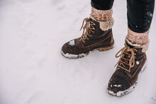 Person In Warm Socks And Boots Standing On Snowy Ground