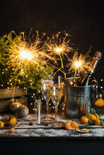 Still Life With Champagne Bottle Standing In A Bucket With Ice, Two Full Flutes, Sparklers And Christmas Ornaments.