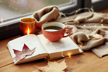 Season, Leisure And Objects Concept - Cup Of Coffee, Book, Autumn Leaves And Candle On Window Sill At Home