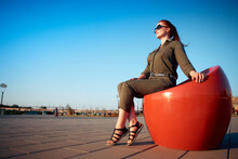 Portrait Of A Purposeful Woman In A Green Jumpsuit And Red Hair Against A Blue Sky, The Concept Of Freedom And Travel