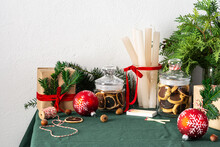Festive Decorated Christmas Or New Year's Table, Thuja And Spruce Branches, Candles And Christmas Balls, Chocolate Chip Cookies In A Jar And Gift Boxes