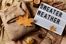 Season And Objects Concept - Wool Clothes, Autumn Leaves, Glasses And Light Box With Sweater Weather Letters On Warm Blankets