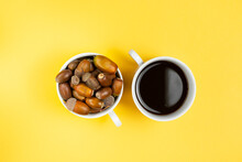 Two White Cups With Alternative Coffee Without Caffeine And Ripe Acorn On Yellow Background