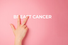 Beat Cancer. A Female's Hand Covers Two Letters In The Word Breast Cancer. Close Up. Pink Background. Breast Cancer Awareness Month