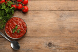 Delicious adjika sauce in bowl with spoon, parsley and tomatoes on wooden table, flat lay. Space for text